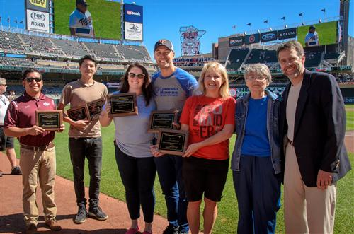 Princiapl Bass (middle) receives a plaque from PeaceMaker MN at the MN Twins Game.