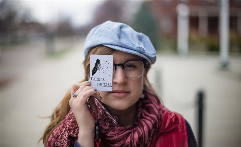 Woman holding a card over her right eye,