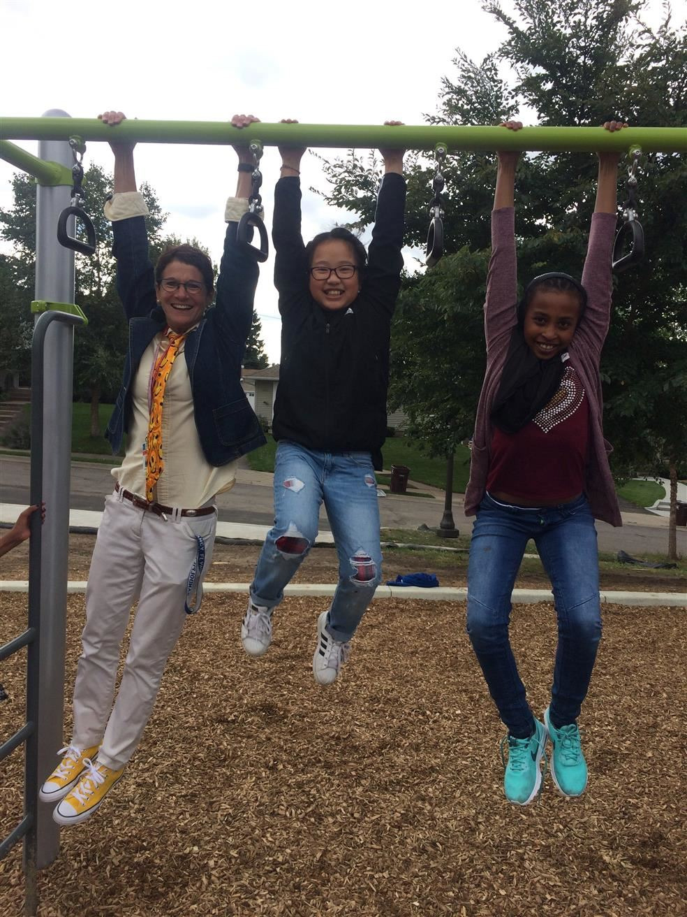 Principal with students on the bars