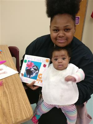 Here is a student displaying her homemade baby book, before reading it to her baby.