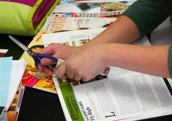 Student cutting out of magazine